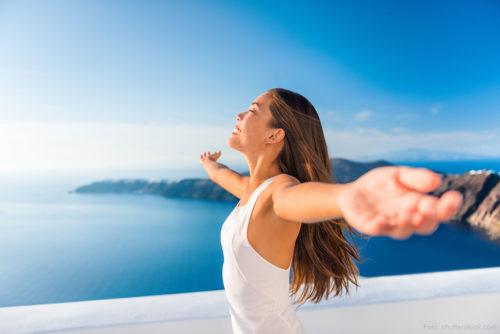 Frau vor blauem Himmel und Meer - lächelt, fühlt sich frei